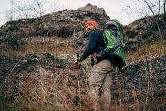 远足在与旅行背包的山的徒步旅行者人背面图 迁徙在他的旅途期间的旅客人 免版税库存照片