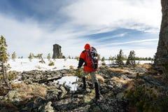 远足在与背包和雪靴的山的冬天 免版税库存图片
