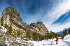 远足在与背包和雪靴的山的冬天 免版税图库摄影