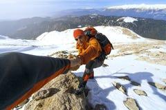 远足在与背包的山的冬天 免版税图库摄影