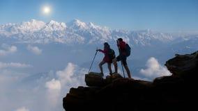 远足在喜马拉雅山山,有放松在山顶部和享受谷的看法背包的远足者 免版税库存照片