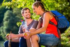 远足在夏天饮用水的夫妇 库存图片