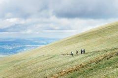 远足在山坡的距离的人们近批评在B的Y爱好者 免版税库存照片