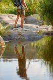 远足在山峰的男性腿 在户外横渡在河小河的远足者脚的迁徙的鞋子岩石石头 库存图片