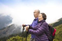 远足在山的愉快的资深夫妇 免版税库存图片