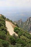 远足在山的道路在莫尼斯特罗尔德莫恩特塞拉特,西班牙临近本尼迪克特的修道院圣玛丽亚de蒙特塞拉特 库存图片