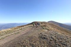 远足在山,旅游业,在山顶部的人们 免版税库存照片