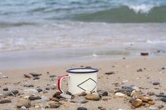 远足在岩石的旅游美丽如画的贝加尔湖的杯子和沙子的上釉的金属在波浪背景的夏天  图库摄影