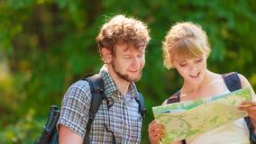 远足在旅行的挑运的夫妇读书地图 库存照片