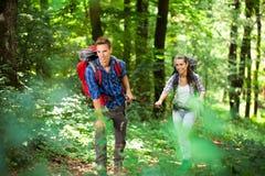 远足在森林里的年轻夫妇 免版税库存图片