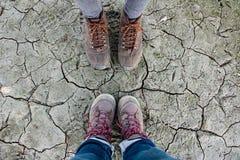 远足在沙漠地面上的鞋子 免版税库存图片