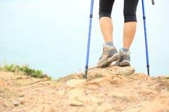 远足在海边岩石的妇女远足者立场 免版税库存照片