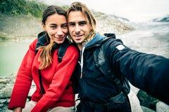 远足在瑞士阿尔卑斯的年轻夫妇,采取Selfie 免版税库存照片