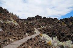 远足在老火山爆发的一个硕大熔岩荒野的道路 免版税图库摄影