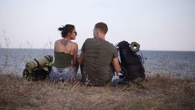 远足夫妇的年轻人基于小山 少妇和人远足者离开背包坐地面享用 影视素材