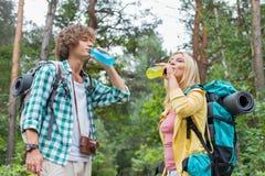 远足夫妇饮用的能量的年轻人在森林里喝 免版税图库摄影