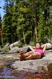 远足女孩放松的睡觉在自然森林里 免版税库存照片