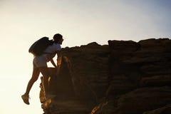 远足妇女上升冠上小山在日落 免版税库存照片