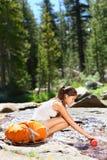 远足妇女饮用水在河在优胜美地 库存照片