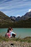 远足孩子在阿尔卑斯临近湖 免版税库存图片