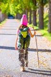 远足孩子女孩有拐棍和背包背面图 免版税库存图片