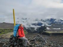 远足山的年轻女人冒险家与重的大在石标风景惊人的风景的背包休息的开会 库存图片