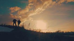 远足帮助的夫妇在山的剪影 远足配合的夫妇,互相帮助,信任协助,日落 影视素材