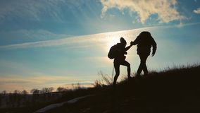 远足帮助的夫妇在山的剪影 远足配合的夫妇,互相帮助,信任协助,日落 股票录像