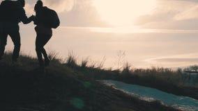 远足帮助的夫妇在山的剪影 远足配合的夫妇,互相帮助,信任协助,日落 股票视频