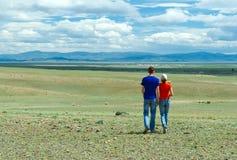 远足干草原的年轻夫妇 库存照片