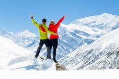 远足成功冬天山的夫妇 库存图片