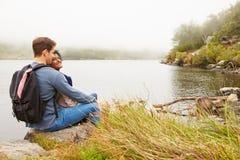 远足放松由湖的边缘的夫妇 库存照片