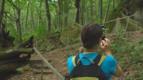远足有做照片的背包的美女由智能手机在山的密林狂放的自然公园 旅行旅游业 影视素材