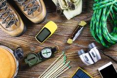 远足有起动的设备,指南针,双筒望远镜,比赛,在木背景的旅行袋子 有效的生活方式概念 免版税库存照片