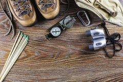 远足有起动的设备,指南针,双筒望远镜,比赛,在木背景的旅行袋子 有效的生活方式概念 库存图片