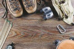 远足有起动的设备,指南针,双筒望远镜,比赛,在木背景的旅行袋子 有效的生活方式概念 库存照片