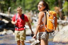 远足朋友有乐趣横穿河在森林 免版税库存照片