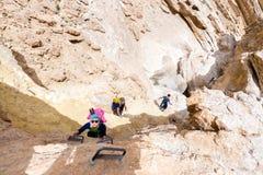 远足沙漠峡谷的小组三个背包徒步旅行者 免版税库存图片