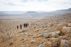 远足沙漠足迹的小组人 库存图片