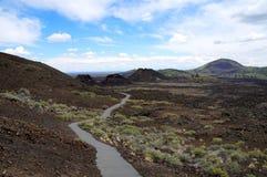 远足沿火山的炭渣和飞溅声锥体链子的道路  免版税库存图片