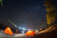 远足游人有休息在他的阵营在晚上在营火附近 库存照片