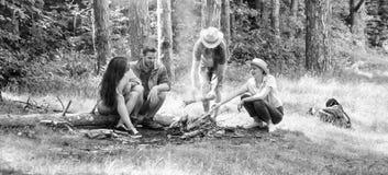 远足烤肉 朋友在朋友去野餐的森林公司中享用周末烤肉或在篝火附近烤烤食物 免版税库存图片