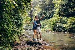 远足由看看法的小河的夫妇 库存图片