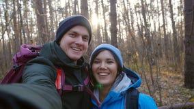 远足的和挑运的概念 年轻愉快的加上背包在森林和制造selfie里 股票视频
