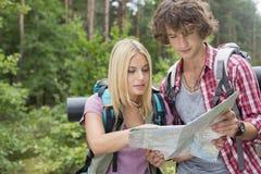 年轻远足的夫妇读书地图一起在森林里 免版税图库摄影