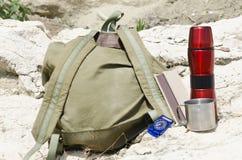 远足的老背包,热水瓶,杯子,在岩石的指南针 远足设备 免版税图库摄影