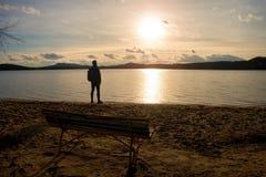 远足者人黑暗的运动服的和有站立在海滩的运动的背包的,放松和享受日落在天际 不可思议的秋天da 库存图片