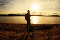 远足者人黑暗的运动服的和有站立在海滩的运动的背包的,放松和享受日落在天际 不可思议的秋天da 免版税库存照片