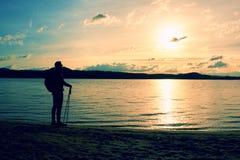远足者人黑暗的运动服的和有站立在海滩的运动的背包的,放松和享受日落在天际 不可思议的秋天da 免版税库存图片