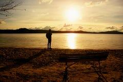 远足者人黑暗的运动服的和有站立在海滩的运动的背包的,放松和享受日落在天际 不可思议的秋天da 图库摄影